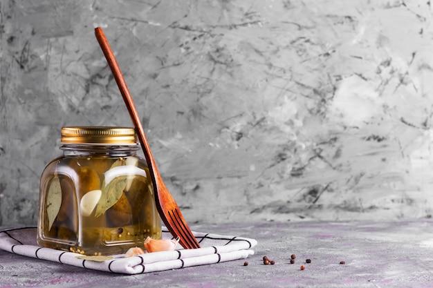 Pepinos enlatados fermentados com folha de louro, alho e endro em uma jarra de vidro com um garfo ecológico de madeira em uma parede cinza