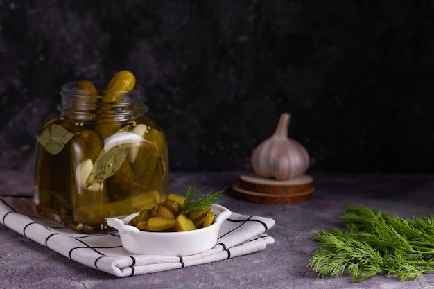 Pepinos enlatados fermentados com folha de louro, alho e endro em uma jarra de vidro com um prato branco com pepino fatiado em um guardanapo branco