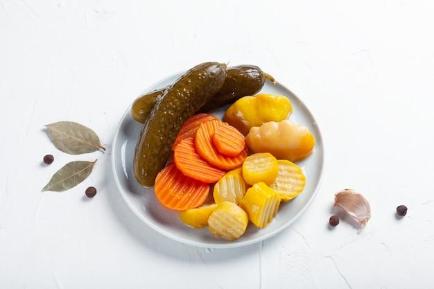 Pepinos fermentados, cenouras e abóbora com ingredientes em uma mesa branca