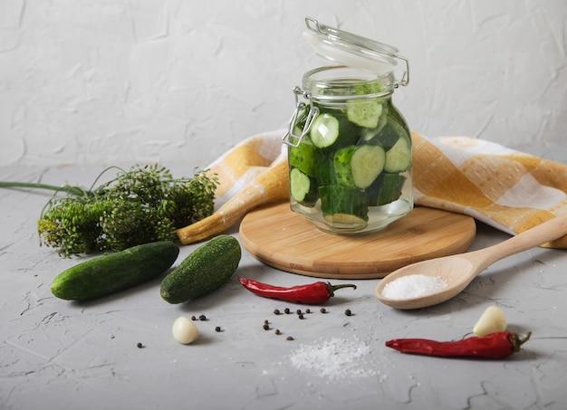 Pepinos fermentados picados em uma jarra de vidro pequena com tampa, pimenta, sal em uma colher de pau ficar em um concreto.