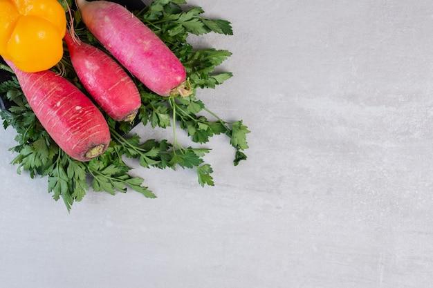 Pepinos frescos, rabanetes vermelhos e pimenta na placa preta. foto de alta qualidade