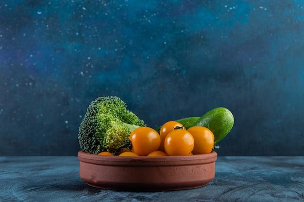 Pepinos frescos, tomate cereja e brócolis em uma tigela de cerâmica.