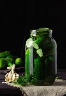 Pepinos levemente salgados em uma jarra de vidro com alho em uma mesa de madeira escura.