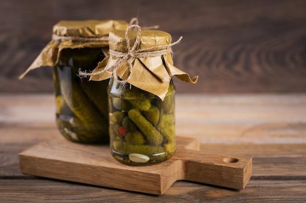 Pepinos marinados com pepino e alho em uma jarra de vidro sobre a mesa de madeira