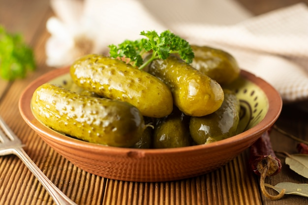 Pepinos marinados. conserva veggies na bacia, tabela de madeira.