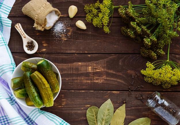 Pepinos salgados. especiarias e ervas para fazer picles. a vista superior da madeira