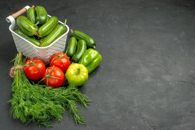Pepinos verdes frescos com verduras e vegetais em fundo escuro de frente
