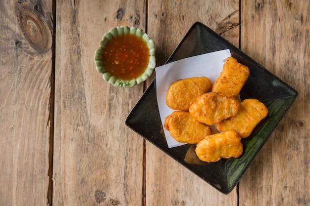 Pepita de galinha com o aperitivo do alimento do molho picante pronto para comer na tabela de madeira.