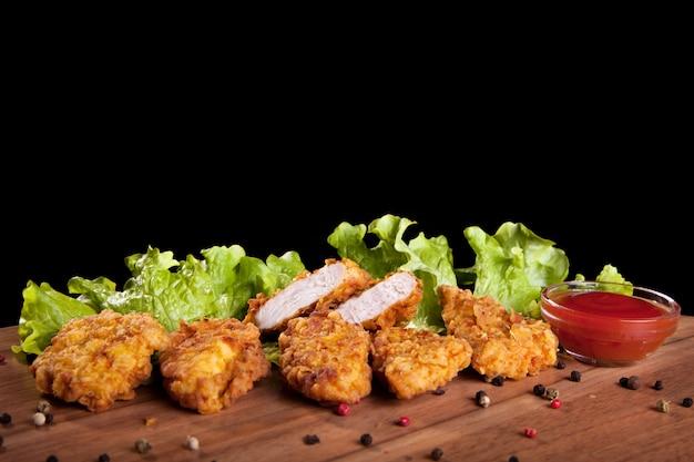 Pepitas de galinha, em uma tabela de madeira com molho e alface no fundo preto.