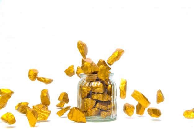 Pepitas de ouro caindo ou minério de ouro e jarra de vidro