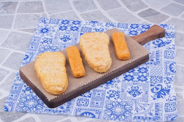 Pepitas de peixe isoladas em uma placa de madeira.