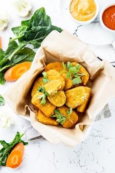 Pepitas saudáveis do vegetariano com cenouras, couve-flor e espinafres. pepitas de legumes.