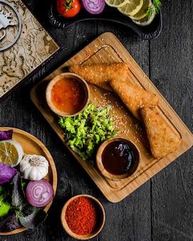 Pepitas servidas com molho de pimentão doce e molho de churrasco