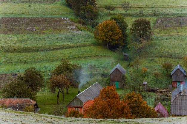 Pequena aldeia de montanha na colina com árvores coloridas verdes, laranja e amarelas