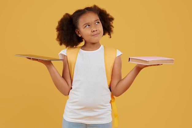 Pequena aluna escolhendo entre tablet e livro