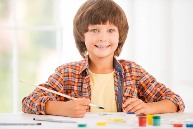 Pequena artista. menino feliz relaxando enquanto pinta aquarelas sentado à mesa