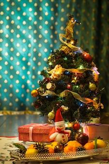 Pequena árvore de natal com enfeites, presentes e frutas cítricas na mesa