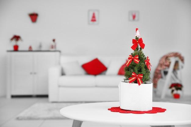 Pequena árvore de natal decorada na mesa da sala, close-up