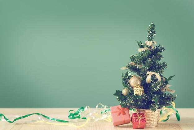 Pequena árvore de natal e caixas com presentes em uma mesa de madeira.
