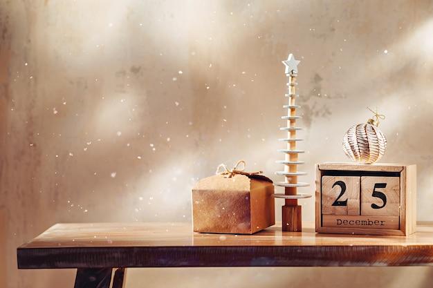 Pequena árvore decorativa de natal com presente, enfeite e calendário de blocos de madeira