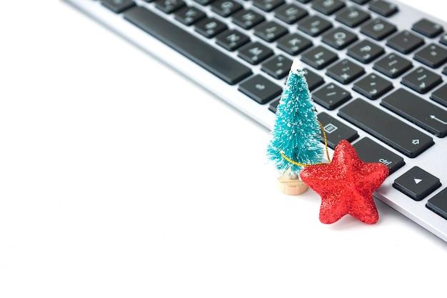 Pequena árvore do abeto e estrela vermelha perto do teclado do computador. clima de natal no local de trabalho.