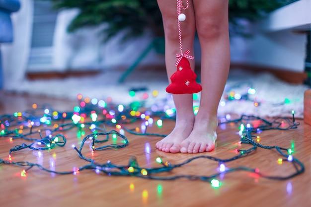 Pequena árvore vermelha nas mãos da encantadora menina cute no fundo luzes brilhantes