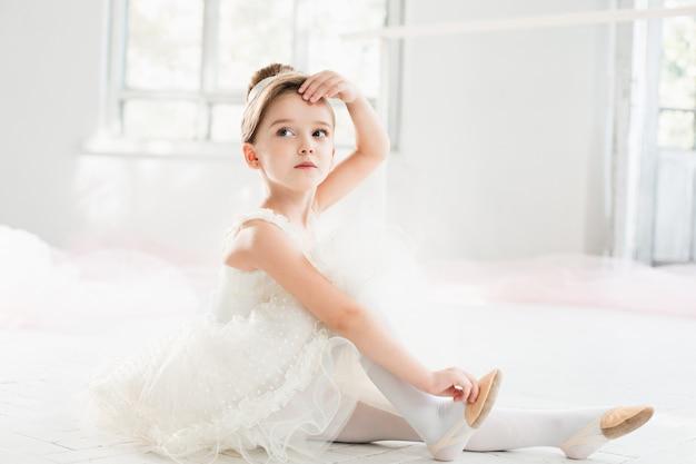 Pequena bailarina com tutu branco na aula na escola de balé