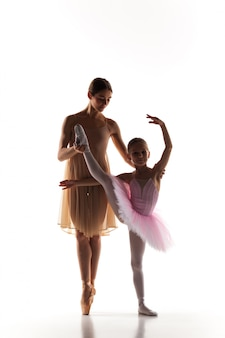Pequena bailarina dançando com professor de balé pessoal no estúdio de dança