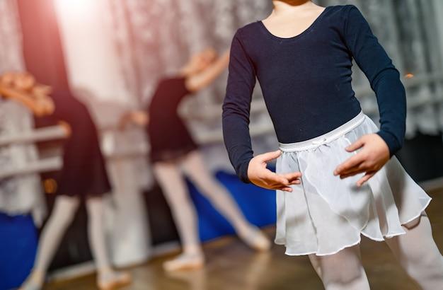 Pequena bailarina em pé em pose com as mãos