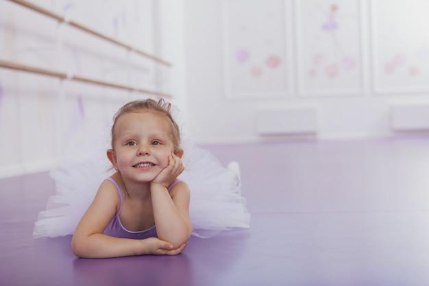 Pequena bailarina encantadora deitada no chão, olhando para longe sonhadora