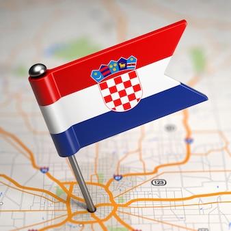 Pequena bandeira da croácia em um fundo de mapa com foco seletivo.
