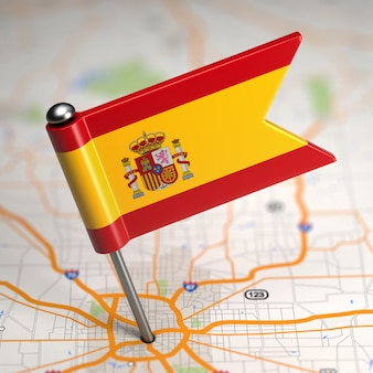 Pequena bandeira da espanha em um fundo de mapa com foco seletivo.