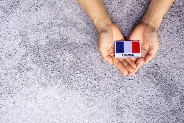 Pequena bandeira da frança em uma mão. conceito de amor, carinho, proteção e segurança.
