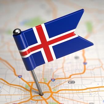 Pequena bandeira da islândia colada no plano de fundo do mapa com foco seletivo.