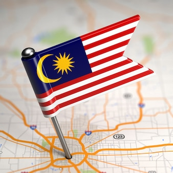 Pequena bandeira da malásia colada no plano de fundo do mapa com foco seletivo.