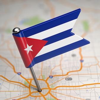 Pequena bandeira da república de cuba em um plano de fundo do mapa com foco seletivo.