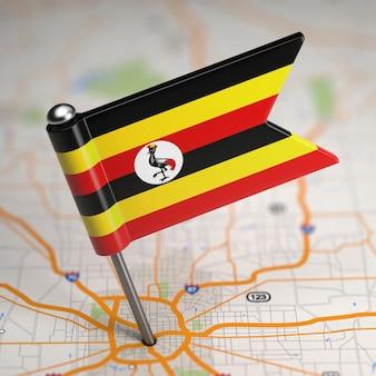Pequena bandeira da república de uganda em um fundo de mapa com foco seletivo.