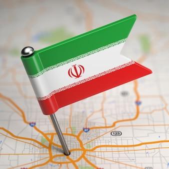 Pequena bandeira da república islâmica do irã em um plano de fundo do mapa com foco seletivo.