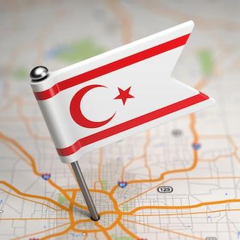 Pequena bandeira da república turca do norte de chipre em um fundo de mapa com foco seletivo.