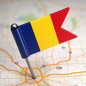 Pequena bandeira da romênia colada no plano de fundo do mapa com foco seletivo.