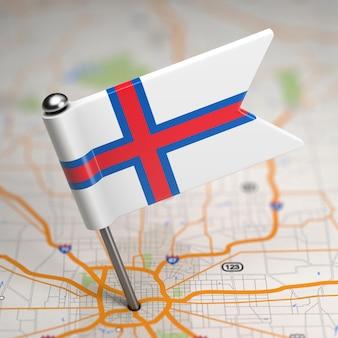 Pequena bandeira das ilhas faroé em um fundo de mapa com foco seletivo.