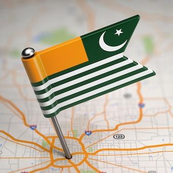 Pequena bandeira de azad kashmir em um fundo de mapa com foco seletivo.