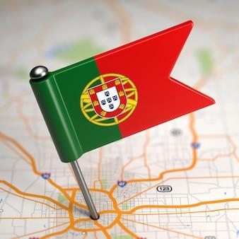 Pequena bandeira de portugal colada no plano de fundo do mapa com foco seletivo.
