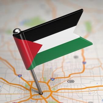 Pequena bandeira do estado da palestina em um fundo de mapa com foco seletivo.