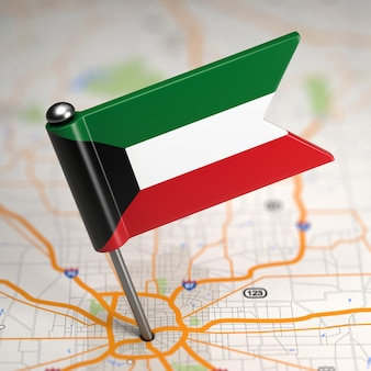 Pequena bandeira do kuwait em um fundo de mapa com foco seletivo.