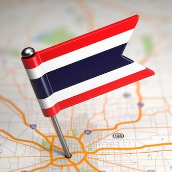 Pequena bandeira do reino da tailândia em um fundo de mapa com foco seletivo.