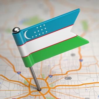 Pequena bandeira do uzbequistão em um fundo de mapa com foco seletivo.