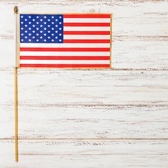 Pequena bandeira dos eua para o dia da independência na mesa de madeira branca