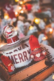 Pequena bola de neve de gnomos fofos com o papai noel no fundo da árvore de natal