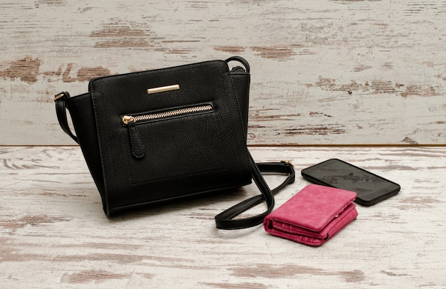 Pequena bolsa feminina preta, bolsa e telefone